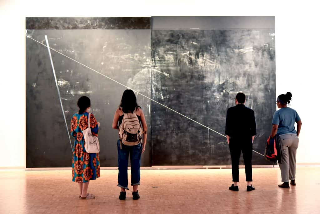 Dyson Opening. Four students looking at large abstract grey piece on wall.