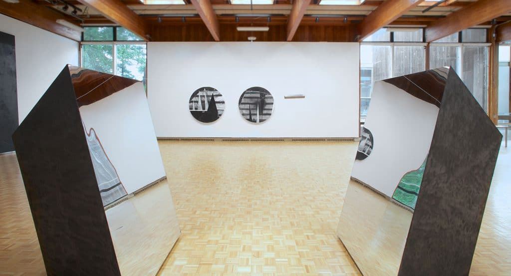 usdan gallery with several works by Torkwase Dyson: two circular canvases and sculptural work of two quadrilateral prisms with one side that is a mirror facing each other.