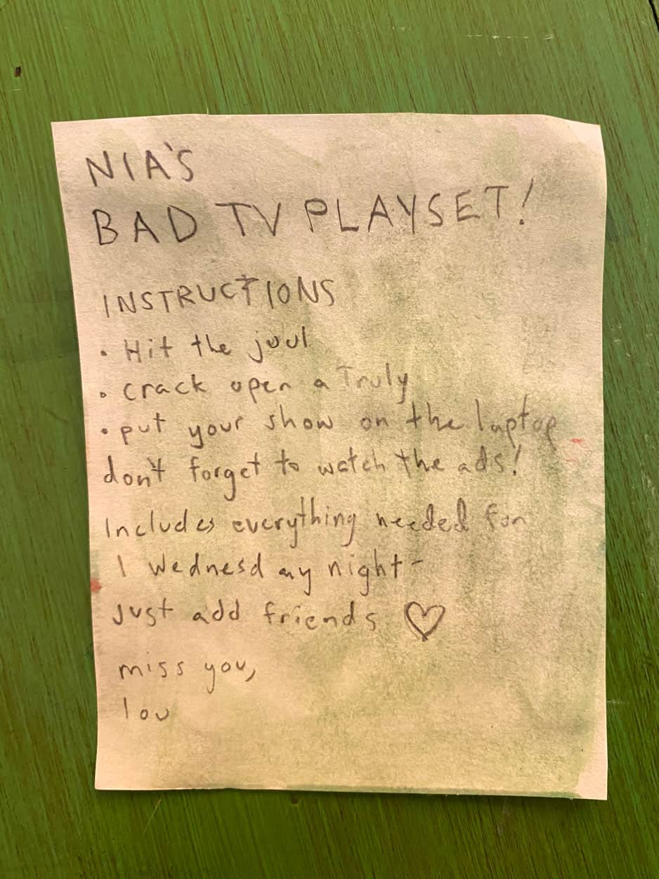 "grey painted piece of paper titled ""Nia's bad tv playset"""