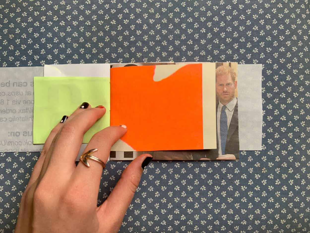 book open to pages of chartreuse colored paper and beige paper with bright orange blob.