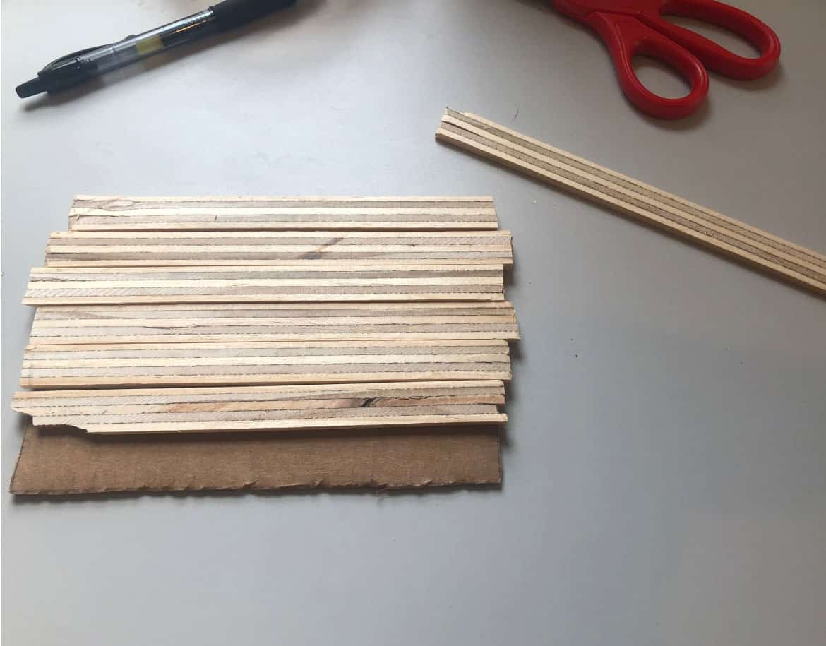 piece of cardboard with strips of wood glued to it
