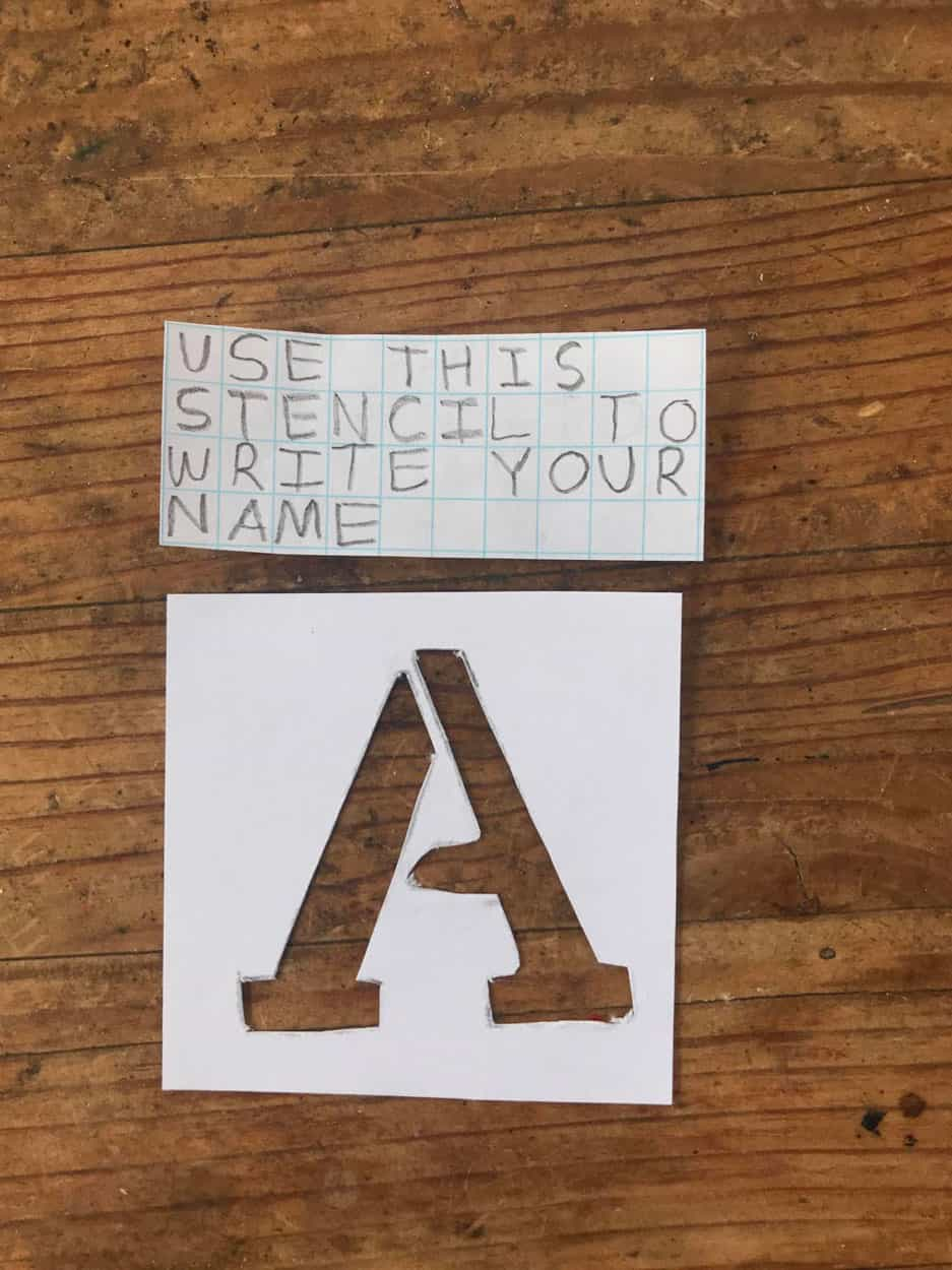 "note reading ""use this stencil to write your name"" and a stencil for a capital A"