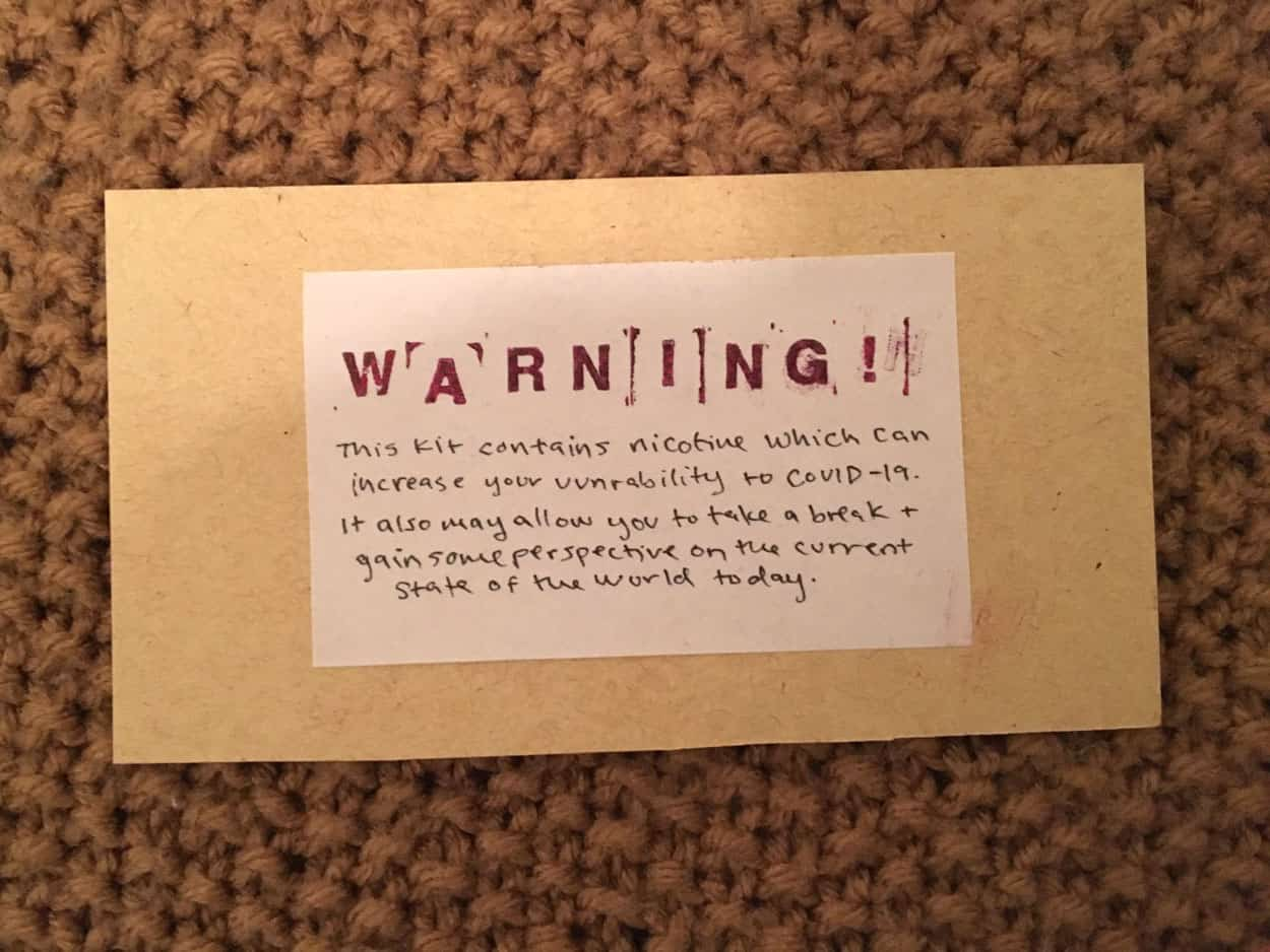 "brown paper card with writing : ""warning! this kit contains nicotine which can increase your vulnerability to COVID-19. It also may allow you to take a break and gain some perspective on the current state of the world today."""