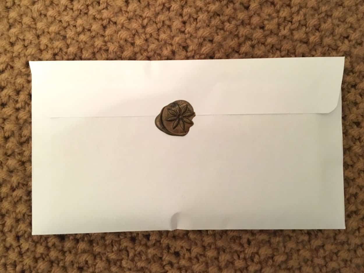 white envelope with wax flower seal on flap