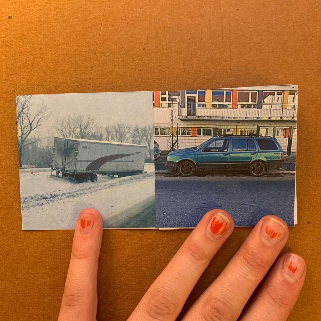 book pages showing a picture of a truck in snow on the left and a blue car on the right.