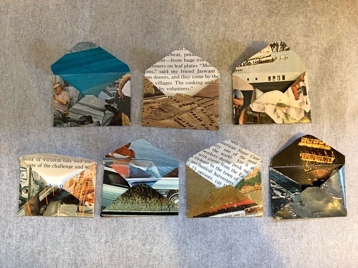 seven small envelopes made of magazine pages. the envelopes are open, exposing text and other photographs on the interior.