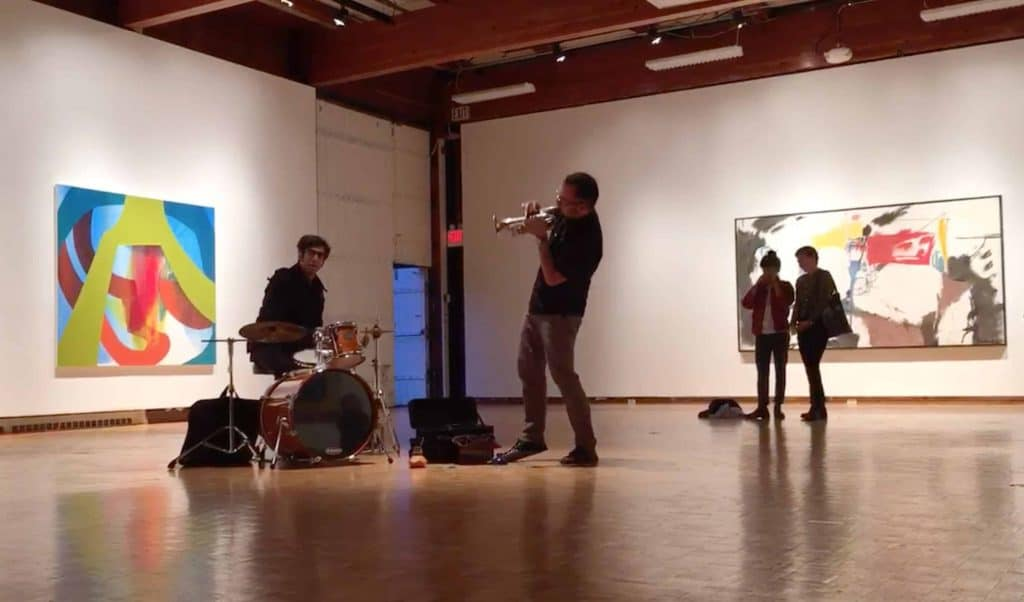 Installation photo of a drummer and a trumpet player. Two viewers watch from the left. In the background, there are two abstract paintings. The one on the right is blue, red, and green. The one of the left is mostly white with red, yellow, and black markings.