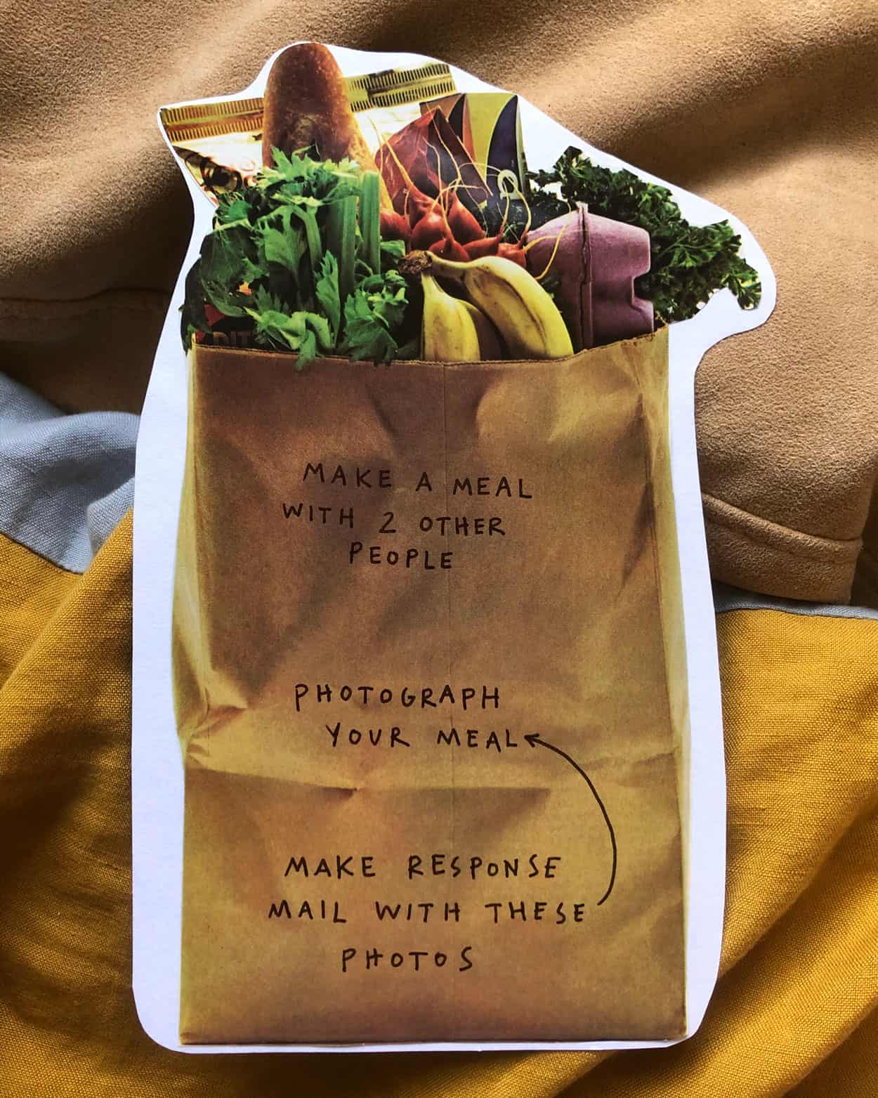 "An organic shaped card, (no shard edges). a photo of a brown paper bag, with groceries . Text on the bag reads: ""make a meal with 2 other people, Photograph you meal, Make a response mail with these photos."""