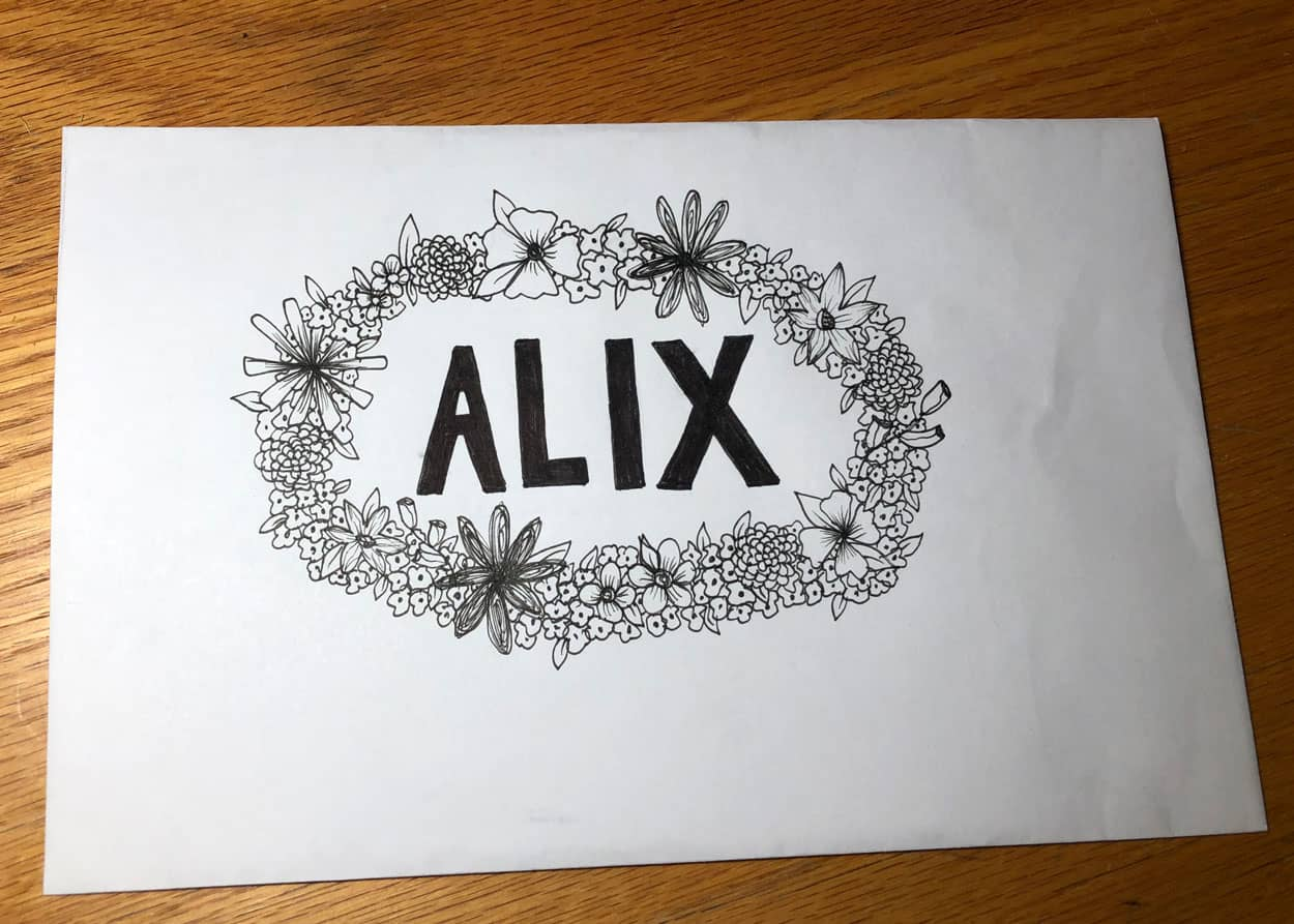 An envelope with With a ring of flowers encircling Alix