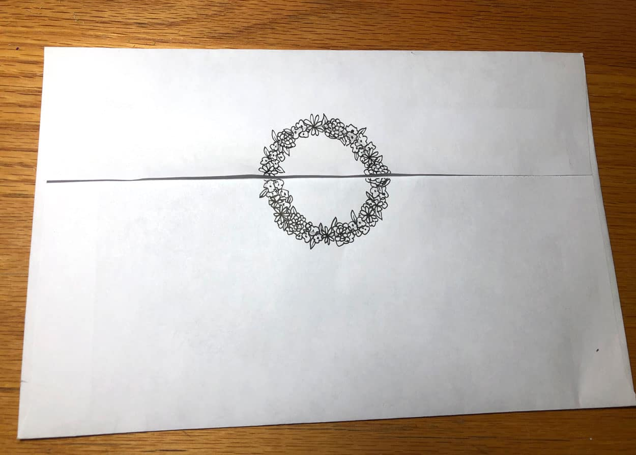 The back of an envelope with a ring of flowers crossing over the flap.