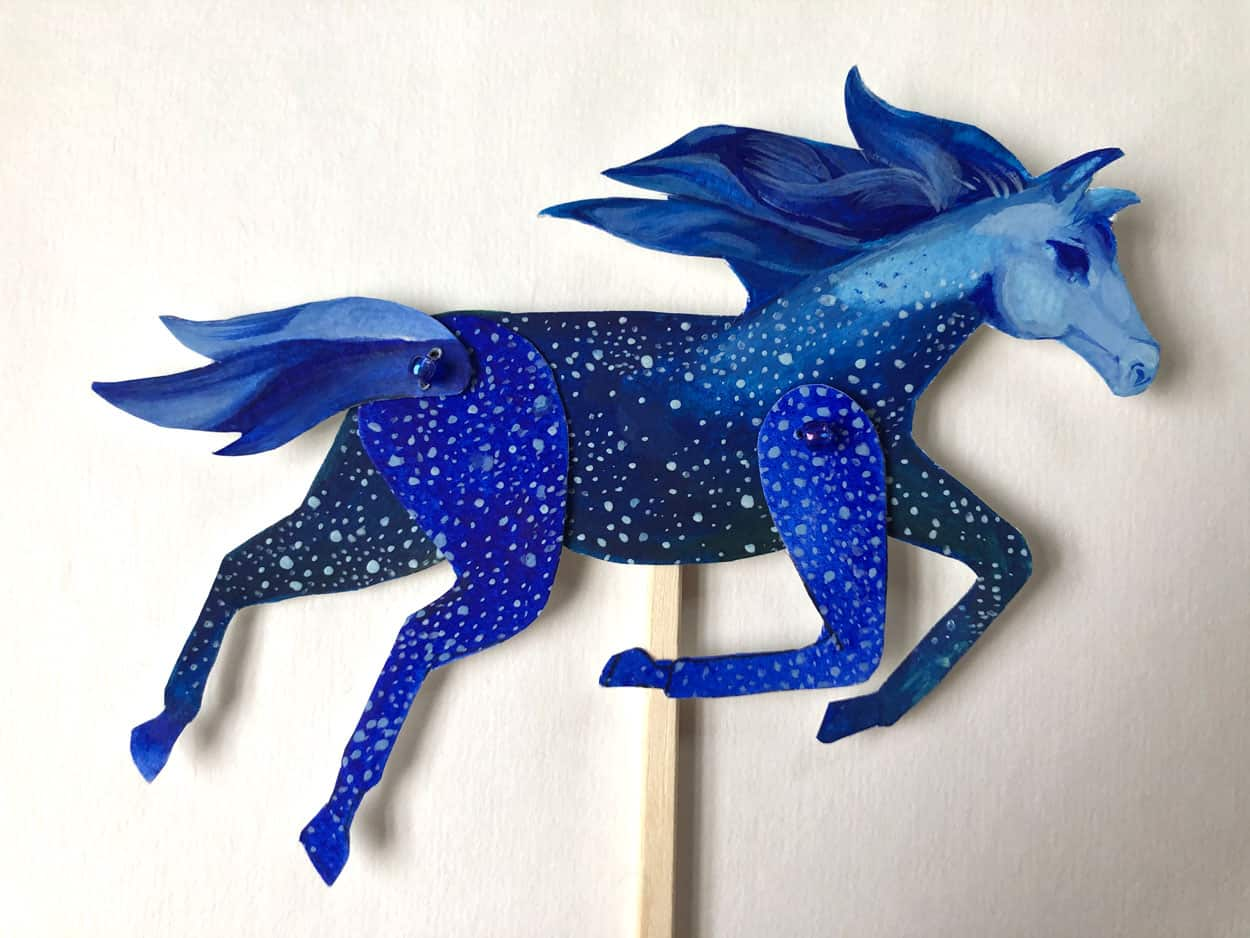 A paper cutout of a horse on a stick. The horse is blue with shite spots resembling stars