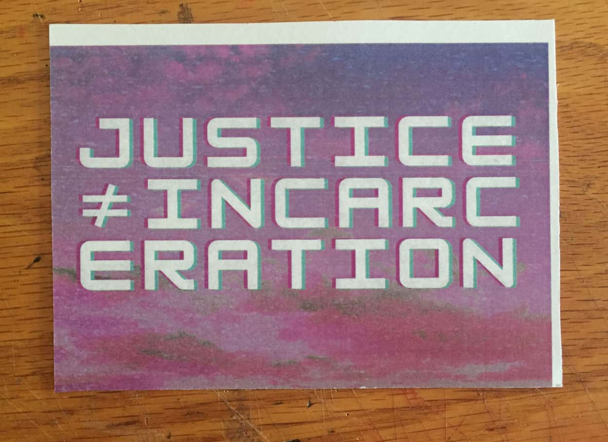 "The words "" justice ≠ Incarceration"" is in white text over a manipulated image of a pink and blue sky."