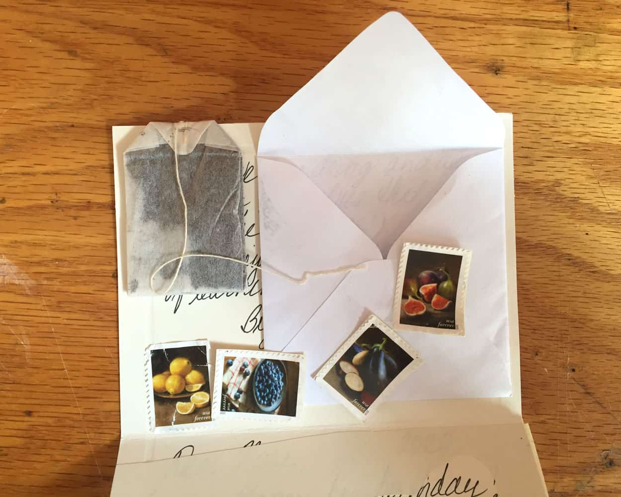 the envelope attached to a letter is open with its contents displayed: a tea bag and stamps depicting fruit.