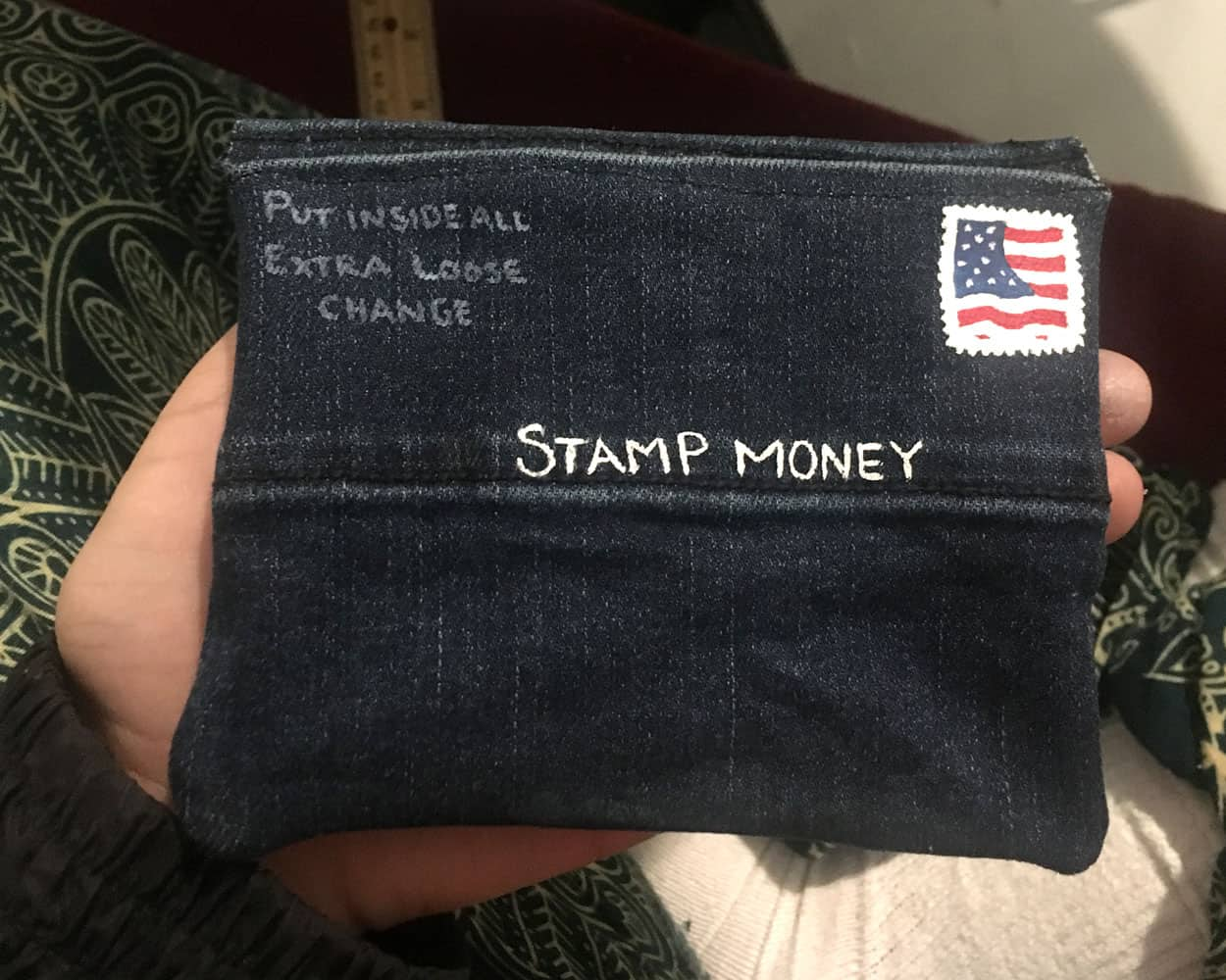 "STAMP MONEY. A denim envelope with the the lettering ""stamp money across the front in white lettering"