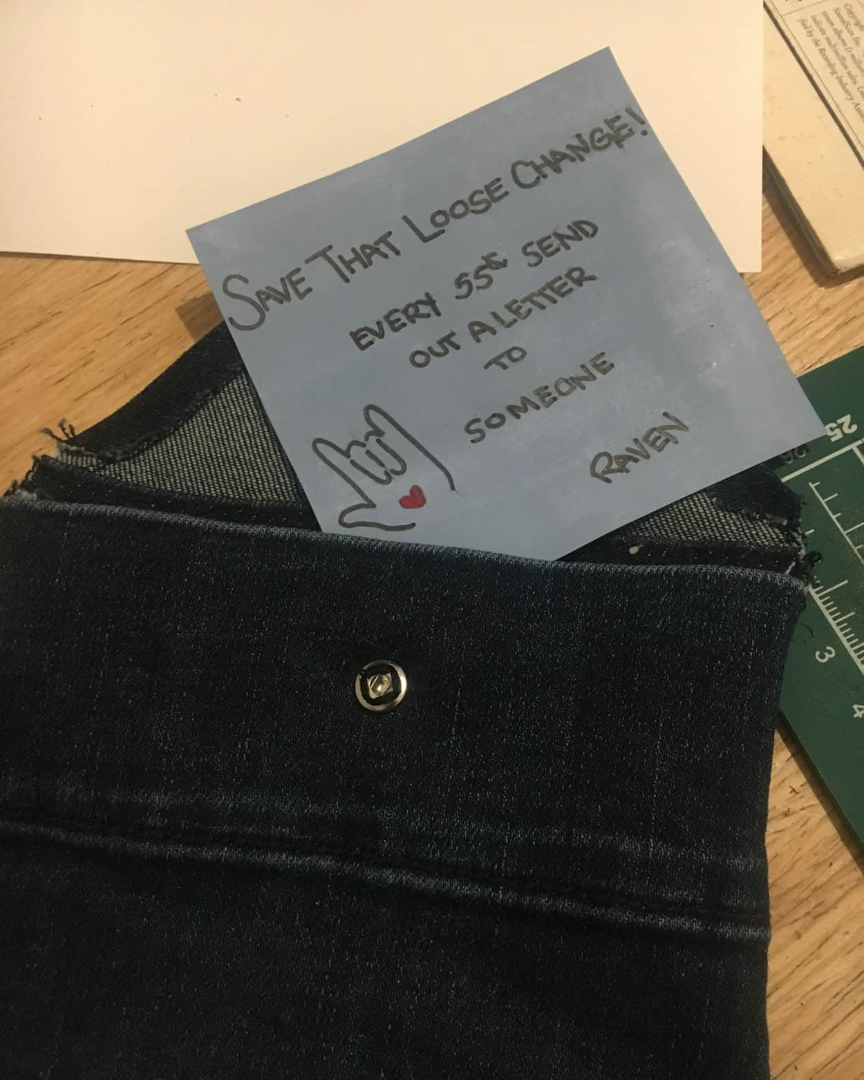 "The denim envelope opened with a blue note sticking out of it. It reads ""save that loose change"""