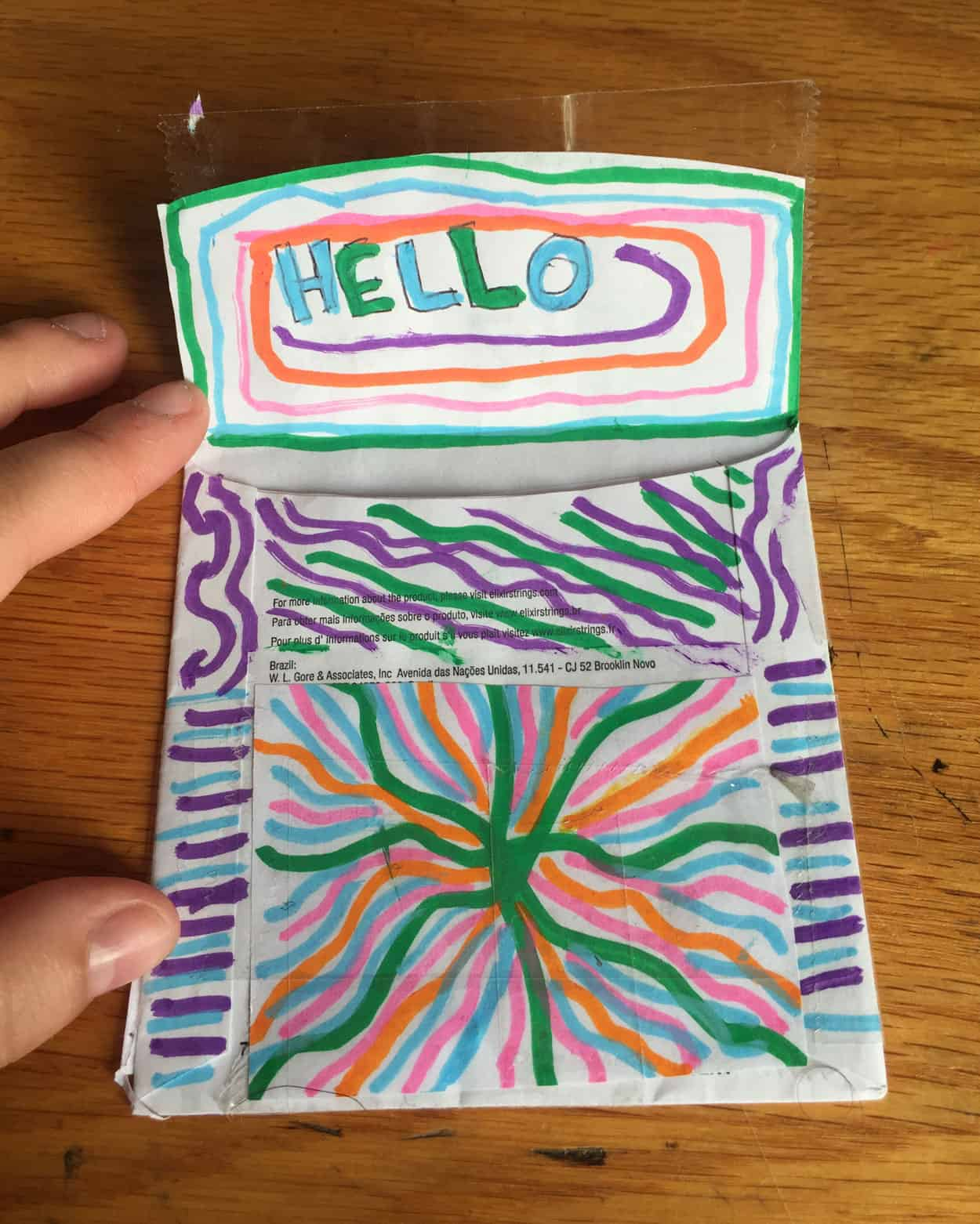 A back of an envelope with the word hello written on the underside of the flap, decorated with green, blue, pink, Orange and purple lines. The Rest of the enveloppe is also decorated in these same colored lines.