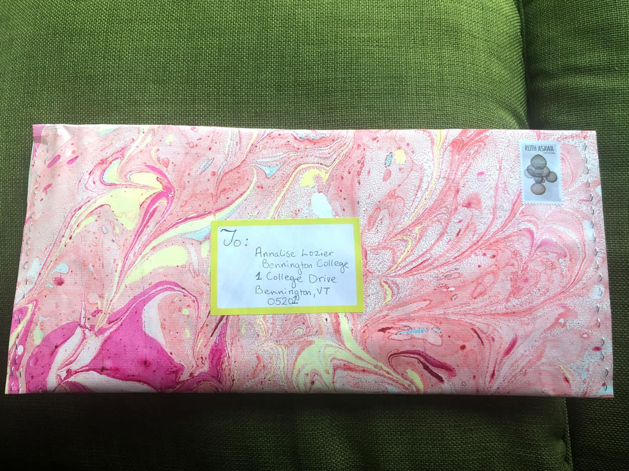 A Marbled pink orange and yellow envelope addressed to Annalise Lozier