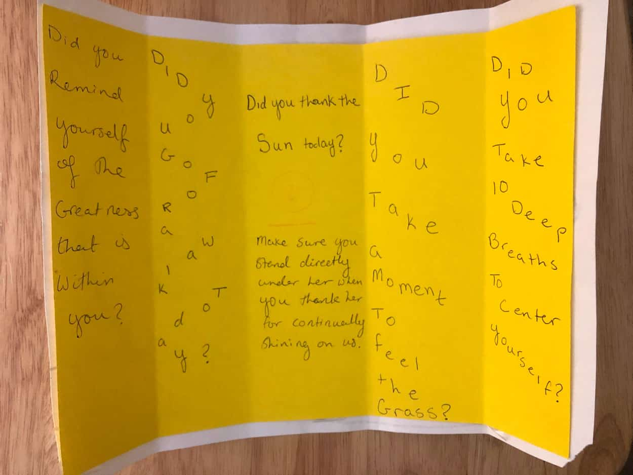 Yellow paper meant to be folded up has handwritten text on it asking questions about self-care.
