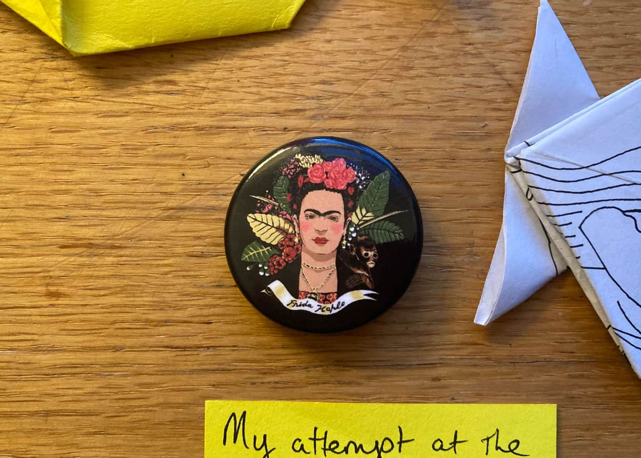 Black metal button pin with a portrait of Frida Kahlo.