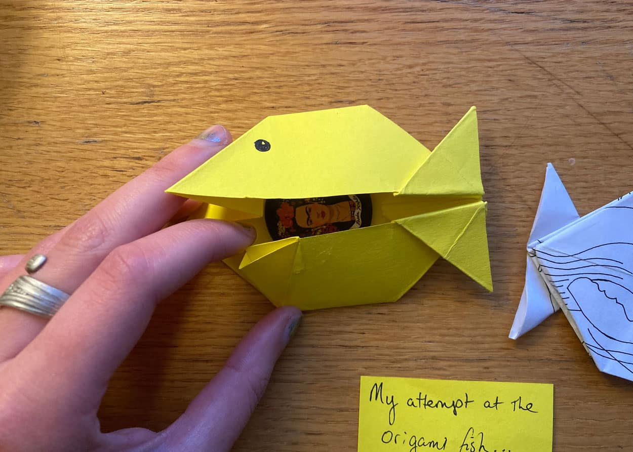 A yellow origami fish being opened with a hand to reveal a small image of Frida Kahlo