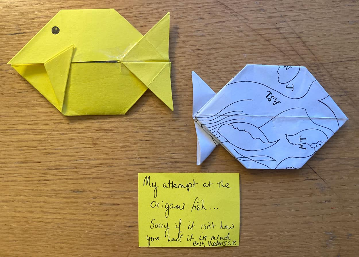 "Two origami fish, one yellow and another made from white paper with some markings on it. A sticky note with text on it below the fish says ""My attempt at the origami fish ... """