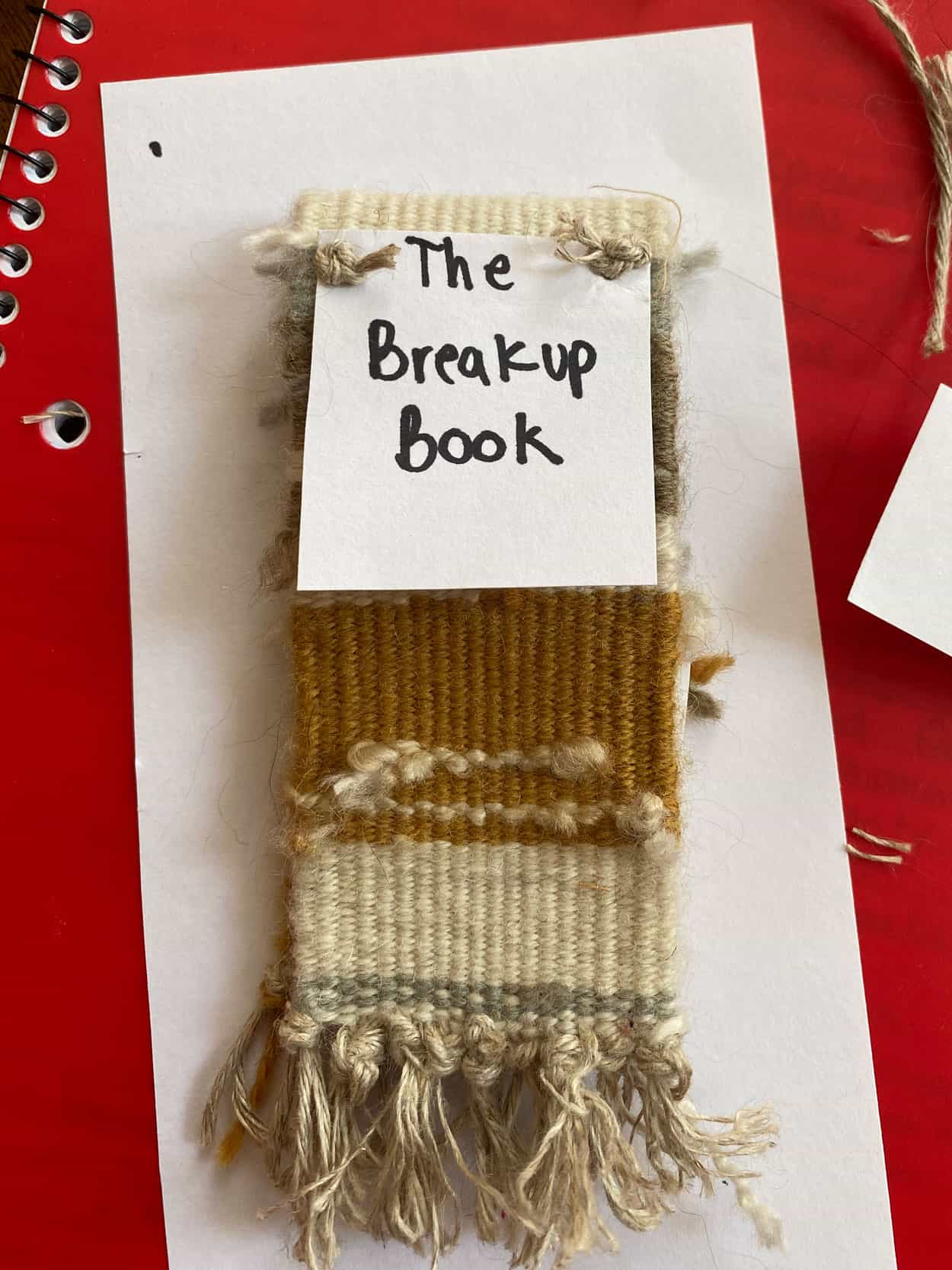 "a woven scrap on a white background, on top of a red notebook. The woven piece is mustard yellow and cream color. The words ""the breakup book"" are on a piece of paper across the top."