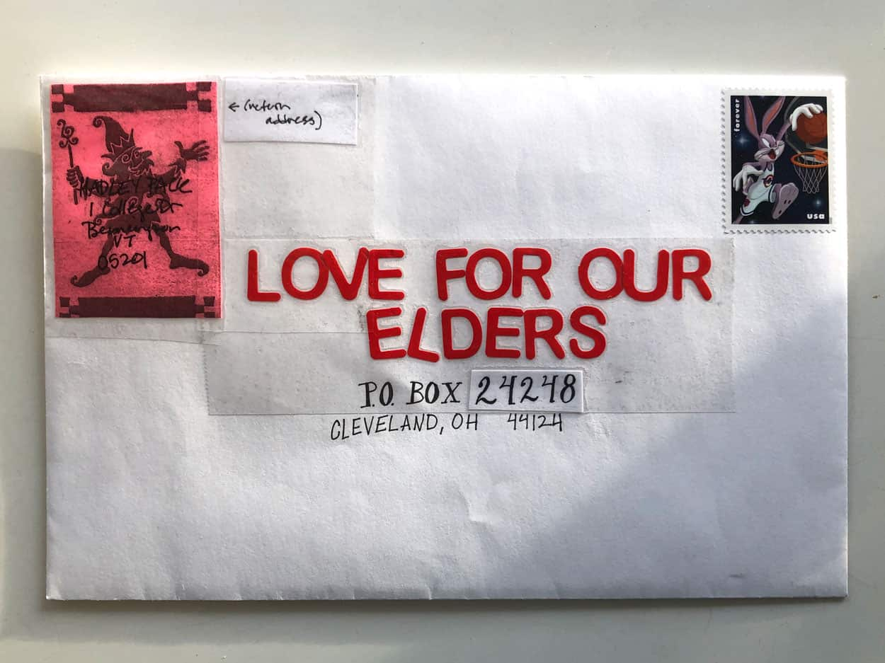 outside of envelope. The letter is addressed to love for our elders, in bold red felt letters taped to the envelope. The return address is written over a image of an elf.